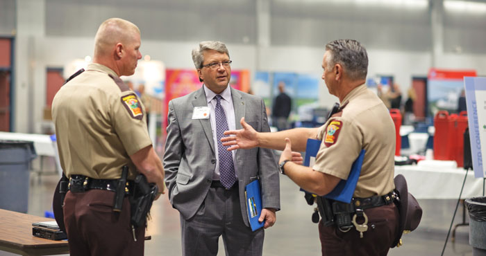 Attendees in the exhibit area speaking with state patrol officials